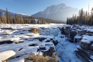 Frozen athabasca falls in the winter with a sun flair
